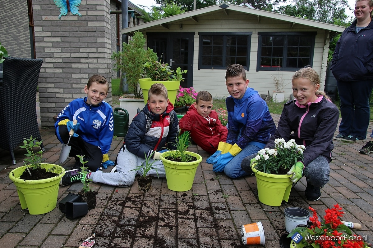 Kinderen helpen bewoners bij het opknappen van hun voortuin
